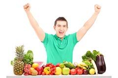 Hombre emocionado que aumenta las manos y que presenta con una pila de fruta Fotos de archivo