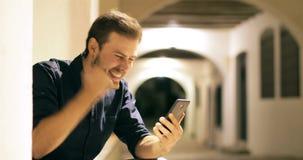 Hombre emocionado que encuentra el contenido en línea del teléfono en la noche almacen de video