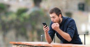 Hombre emocionado que encuentra el contenido en línea en un teléfono