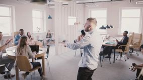Hombre emocionado que entra en la oficina multiétnica, haciendo danza divertida de la celebración para compartir éxito con la cám almacen de metraje de vídeo