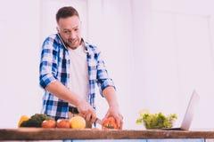 Hombre emocionado que hace su mejor para cocinar algo delicioso foto de archivo libre de regalías