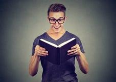 Hombre emocionado que mira el libro fotografía de archivo