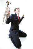 Hombre emocionado que se arrodilla con la trompeta a disposición y que grita. Aislante Foto de archivo libre de regalías