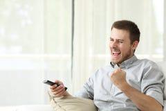 Hombre emocionado que ve la TV Foto de archivo