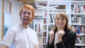 Hombre emocionado y mujer que reaccionan al éxito en el trabajo en oficina almacen de metraje de vídeo
