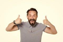 Hombre emocional con dos pulgares para arriba aislados en el fondo blanco Emoción feliz de la cara del individuo barbudo emociona imagenes de archivo