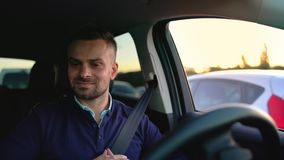 Hombre emocional que conduce en coche automatizado innovador usando el piloto automático del uno mismo-estacionamiento para parqu almacen de video