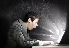 Hombre emocional que usa el ordenador portátil Imágenes de archivo libres de regalías