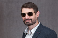 Hombre en años 40 con una barba llena y las gafas de sol Fotografía de archivo libre de regalías