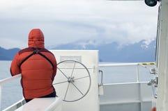 Hombre en abajo abrigo esquimal en el barco de Alaska Foto de archivo