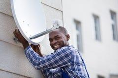 Hombre en antena parabólica uniforme de la colocación TV foto de archivo libre de regalías