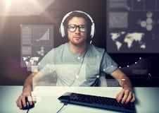 Hombre en auriculares con el ordenador sobre las pantallas virtuales Imagen de archivo
