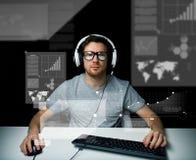 Hombre en auriculares con el ordenador sobre las pantallas virtuales Fotografía de archivo