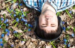 Hombre en auriculares. Flores. Resorte Imagen de archivo libre de regalías