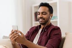 Hombre en auriculares que escucha la música en smartphone fotos de archivo