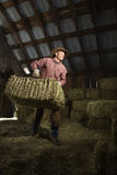 Hombre en balas móviles del granero de heno Imágenes de archivo libres de regalías