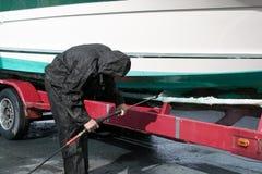 Hombre en barco que se lava del traje protector Imágenes de archivo libres de regalías