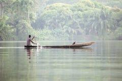 Hombre en barco tradicional en el río tropical Volta en Ghana, A del oeste imagen de archivo