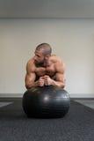 Hombre en bola de la aptitud que ejercita el ABS Imagen de archivo