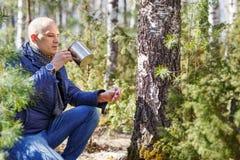 Hombre en bosque que bebe de la savia del árbol de la taza Foto de archivo