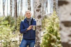 Hombre en bosque que recoge la savia del abedul Foto de archivo