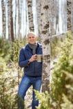 Hombre en bosque que recoge la savia del abedul a la capacidad Fotografía de archivo libre de regalías
