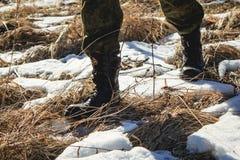 Hombre en botas que camina en nieve Fotografía de archivo