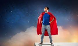 Hombre en cabo rojo del super héroe sobre el cielo nocturno fotos de archivo