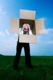 Hombre en caja de cartón Imagen de archivo libre de regalías