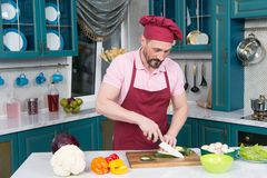Hombre en calabacín uniforme del corte del delantal en rebanada por el cuchillo La paprika anaranjada y roja en la tabla se prepa imagen de archivo