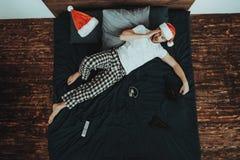 Hombre en cama con dolor de cabeza después de la fiesta de Navidad foto de archivo