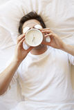 Hombre en cama con el despertador en Front Of Face Fotografía de archivo