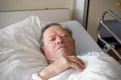 Hombre en cama de hospital foto de archivo libre de regalías
