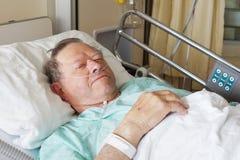 Hombre en cama de hospital Fotos de archivo libres de regalías