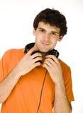 Hombre en camisa anaranjada con los auriculares que escucha la música - aislada en blanco Foto de archivo