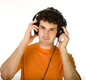 Hombre en camisa anaranjada con los auriculares que escucha la música - aislada en blanco Imagen de archivo
