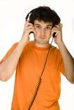 Hombre en camisa anaranjada con los auriculares que escucha la música - aislada en blanco Fotografía de archivo