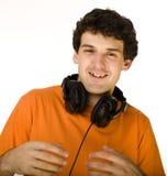 Hombre en camisa anaranjada con los auriculares que escucha la música - aislada en blanco Fotografía de archivo libre de regalías
