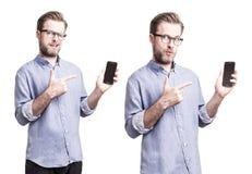 Hombre en camisa azul que señala en el smartphone del teléfono móvil Foto de archivo