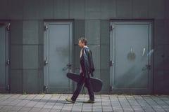 Hombre en camisa de manga corta que camina con la caja de la guitarra Imágenes de archivo libres de regalías