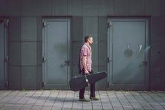 Hombre en camisa de manga corta que camina con la caja de la guitarra Fotografía de archivo