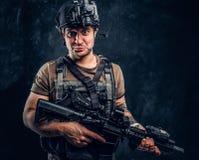 Hombre en camiseta con el tatuaje en su armadura que lleva de la mano y casco con una visión nocturna que sostiene el rifle de as fotos de archivo