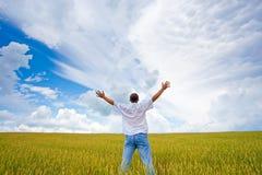 Hombre en campo bajo los cielos imagen de archivo libre de regalías
