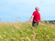 Hombre en campo con la brisa imagenes de archivo