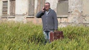 Hombre en campo con la maleta que habla en el teléfono metrajes