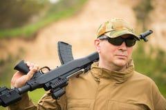 Hombre en camuflaje con una escopeta Fotografía de archivo