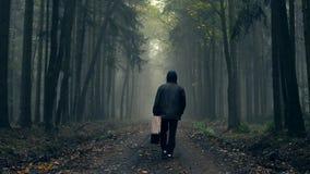 Hombre en capa con la maleta vieja en un bosque de niebla del otoño almacen de video