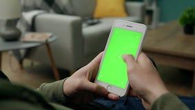 Hombre en casa Sitng en un sof? usando Smartphone con la pantalla verde de la maqueta almacen de video