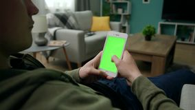 Hombre en casa Sitng en un sof? usando Smartphone con la pantalla verde de la maqueta metrajes