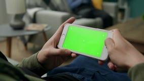 Hombre en casa Sitng en un sof? usando Smartphone con la pantalla verde de la maqueta almacen de metraje de vídeo